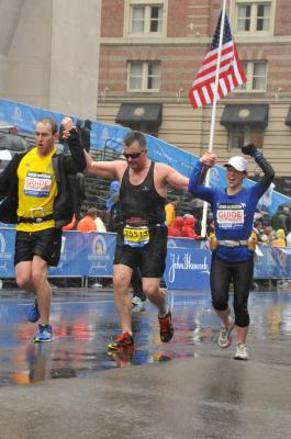 Photo left to right, Christopher, Gaston and Melany approaching the Boston Marathon finish line, April 2015.