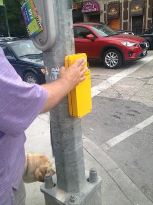 Photo of a street pole with a yellow push button and a person's hand touching to activate the APS.