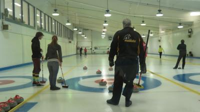 Photo of curlers from behind the house, Skip Ross Martin wearing Manitoba jacket.