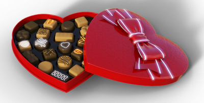 Photo of an open box of heart shaped chocolates with a beautiful red and white bow on the top of the box. The left side of the box shows the yummy chocolates to share.