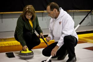 Photo of Curling Coach showing a VI Curler how to hold the curling rock.