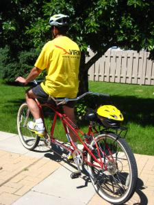 Photo of tandem bike with a pilot in front seat with a helmet on the back seat ready for you to hop on.