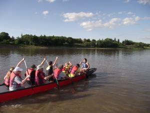 Photo of the front five rows with two people per row and paddles up paddling down the river.