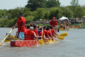 Photo of a dragon boat team paddling on the water.