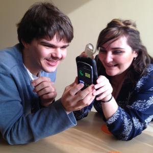 Photo of two a young man and young lady sharing information by tapping their iPhones together.