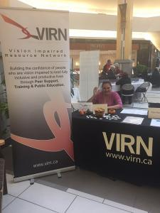 Photo of Tasia waving hi and sitting behind a VIRN display table.