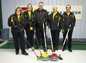 Photo of team Manitoba 1 standing around curling rocks